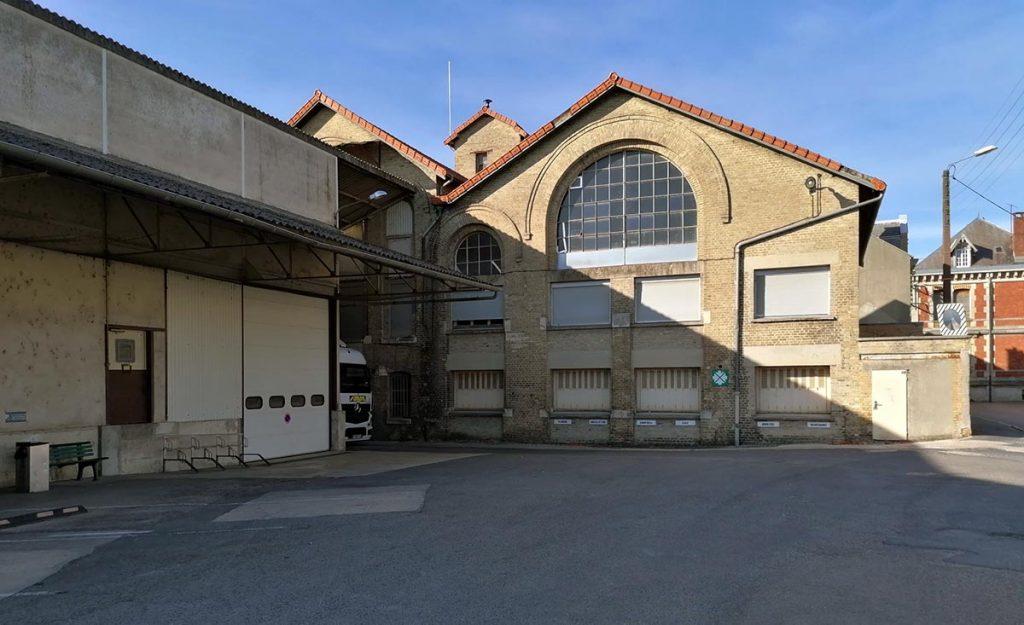 La cour de l'usine Smurfit Kappa avec les anciens bâtiments à grandes baies vitrées